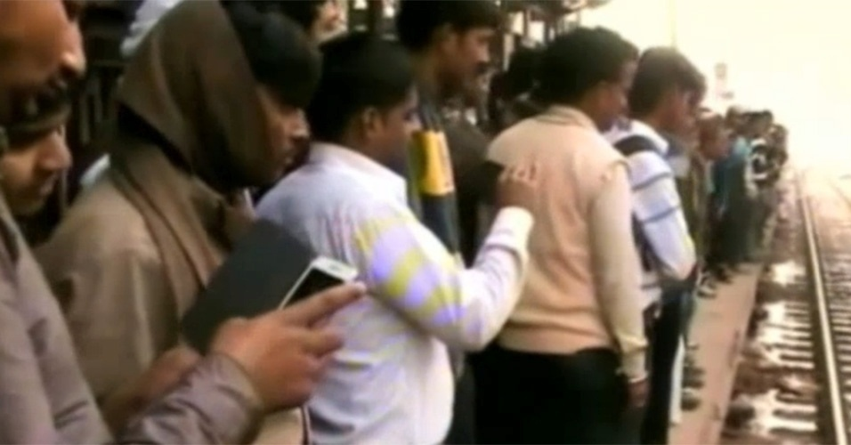 """21.dez.2014 - Em uma estação de trem na cidade de Kanpur, no norte da Índia, uma multidão olha surpresa como um macaco chega para resgatar um """"colega"""" que está caído inconsciente. Ele tomou um choque enquanto andava em fios de alta tensão no local."""