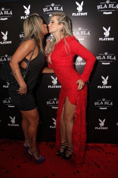 14.abr.2015 - Veridiana Freitas (à direita), capa da edição de abril, dá um selinho em Dani Sperle (à esquerda). A loira, que usava um look vermelho avaliado em cerca de R$ 100 mil, é a capa da Playboy de abril