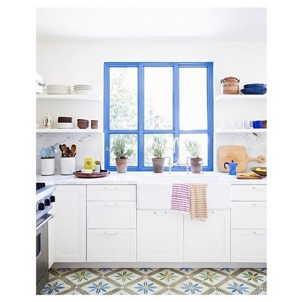 Na imagem, uma cozinha projetada Heather Taylor Home em Los Angeles. Detalhe para as janelas de cores azuis acompanhadas de pequenos vasos. A foto foi postada no Instagram Décor Aid