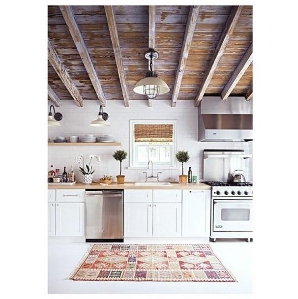 Tetos de madeira rústicas e lustres em estilo vintage fazem a diferença na decoração desta cozinha. A imagem foi compartilhada no Instagram Décor Aid
