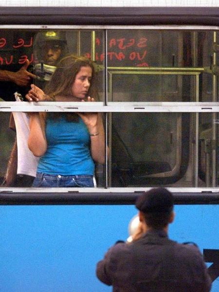 12.jun.2000 - O sequestrador Sandro do Nascimento aponta arma para a cabeça da refém Luana Guimarães, na janela do ônibus 174, no Rio - Antonio Sforza / AFP Photo