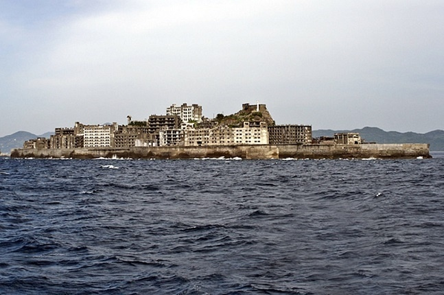 """16.jun.2015 - O Japão abriga uma das mais populares """"ilhas fantasmas"""" do mundo. Construída em 1890 e abandonada completamente em 1974, a ilha de Hashima, no litoral do país asiático, servia como base e alojamento de trabalhadores da indústria de extração de carvão das profundezas do oceano. Em seu """"boom imobiliário"""" chegou a ter 5.259 moradores, que foram abandonando a ilha conforme o carvão ia sendo substituído pelo petróleo. Desde então, a ilha foi desativada e chama a atenção apenas dos fãs de locais abandonados"""