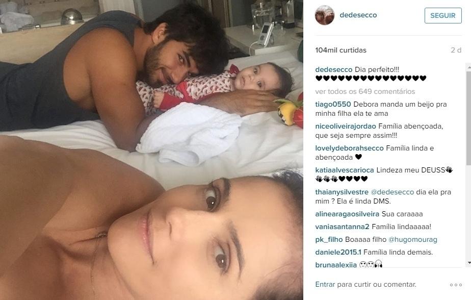 1.mai.2016 - Deborah Secco compartilhou mais um de seus belos momentos em família ao lado de Hugo Moura e Maria Flor. À vontade na cama, o papai aparece agarradinho com a filha na foto