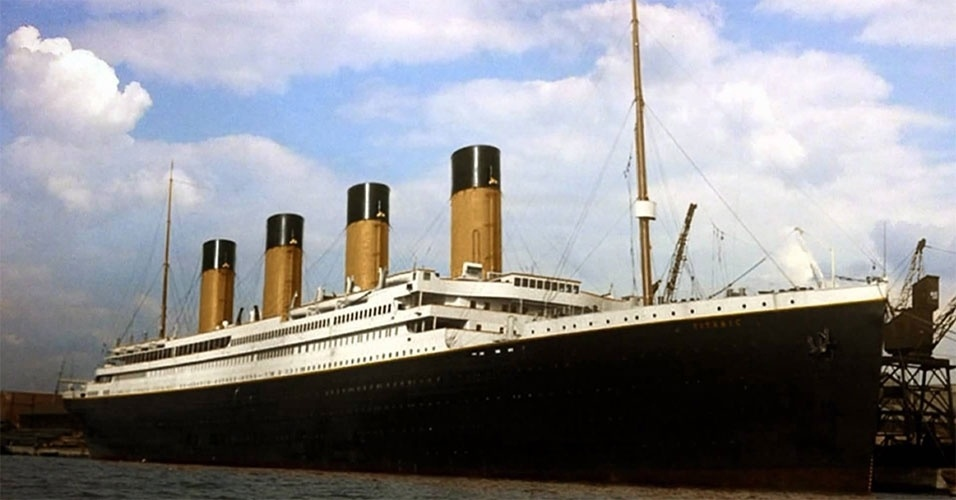 """Considerado """"inafundável"""", o navio RMS Titanic, um colosso marítimo de 269 metros de comprimento e 46 mil toneladas, afundou em sua viagem inaugural após colidir com um iceberg no Oceano Atlântico, na noite do dia 14 de abril de 1912, após partir de Southampton, na Inglaterra, com destino a Nova York, Estados Unidos. Das cerca de 2200 pessoas a bordo (contando com a tripulação de quase 900 homens), mais de 1500 morreram nas águas gélidas da região de Newfoundland, muitas delas devoradas por tubarões (aproximadamente 800 pessoas)"""