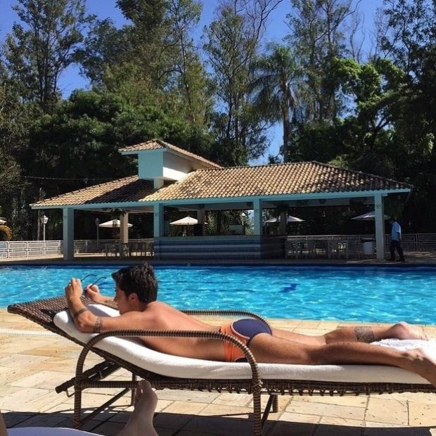 """28.jun.2015 - Sem camiseta, Thammy Miranda mostrou uma prévia do resultado de sua cirurgia de retirada dos seios. Usando apenas uma sunga, a foto mostra Thammy deitada de bruços em uma cadeira à beira da piscina. """"Bom dia! Deus abençoe vocês"""", escreveu ela na legenda da imagem"""