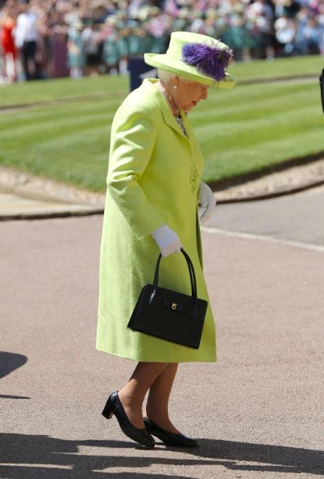 A rainha Elizabeth 2ª usa um vestido verde com detalhe roxo no chapéu para o casamento do neto Harry