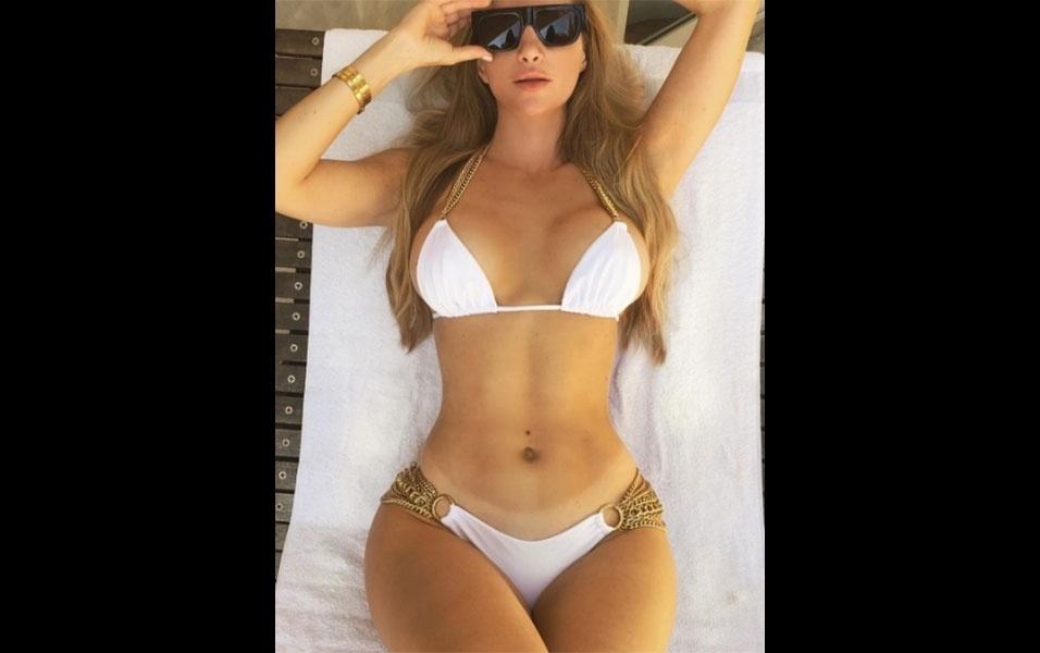 """3.jul.2016 - A modelo Amanda Lee mostrou porquê é uma das musas fitness que mais chama atenção e ganha seguidores no Instagram. A gata postou uma foto em que aparece de biquíni branco, exibindo o corpinho escultural que tanto atrai patrocínios para a gata, uma das modelos mais bem pagas da rede social. Além do corpo """"violão"""", chama atenção também uma marquinha de biquíni pra lá de indiscreta na gata"""