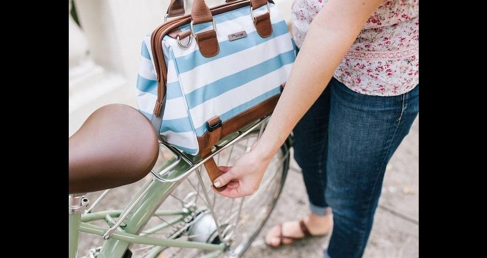 31. O modelo de bolsa para o banco de carona possui fechamento por cinto e pode ser facilmente utilizado como acessório de moda