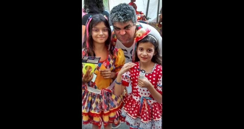 João Dufrayer com as filhas Bárbara, sete anos, que está usando um vestido com bolinhas vermelhas e brancas, e Scarlett, oito anos, que está usando um vestido com tons amarelos, na festa junina do Centro Cultural João Nogueira - Imperator, de Méier, no Rio de Janeiro (RJ)