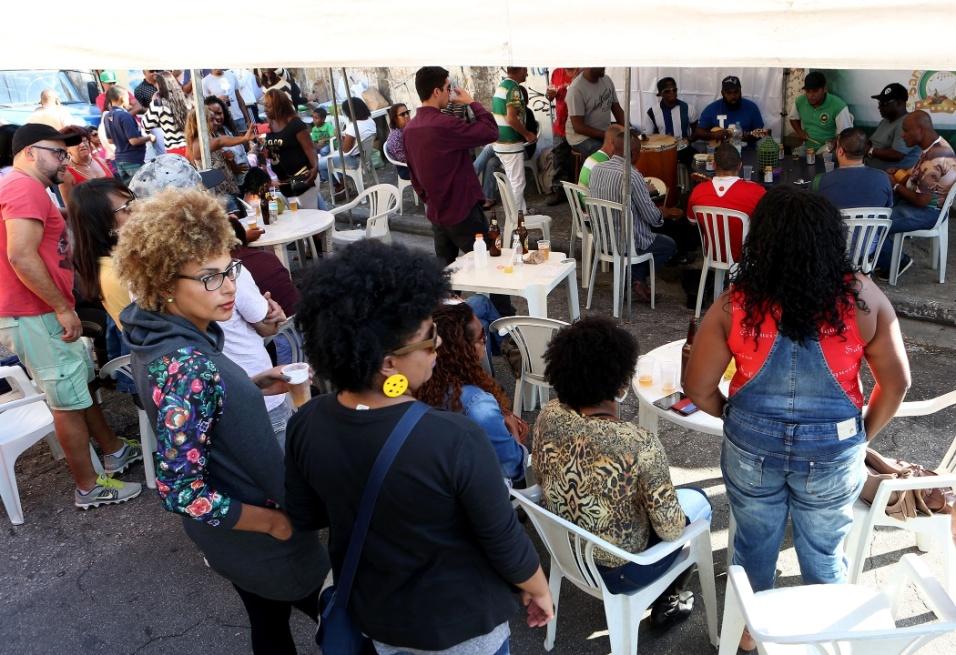 20.mai.2016 - Samba na feira. De pé ou sentado, o público se aproxima da tenda montada no Jardim Primavera, na zona norte de São Paulo, e curte canções da Velha Guarda cantadas pelos músicos do Samba na Feira