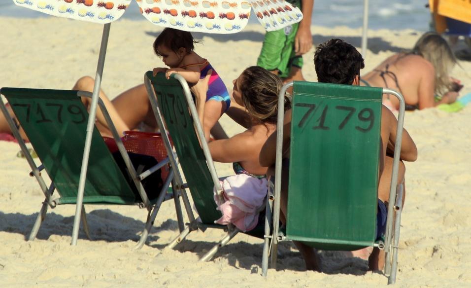 1º.ago.2016 - Maria Flor brinca de escalar a cadeira de praia ao lado da mãe, a atriz Deborah Secco e do papai, Hugo Moura, na praia da Barra da Tijuca, no Rio