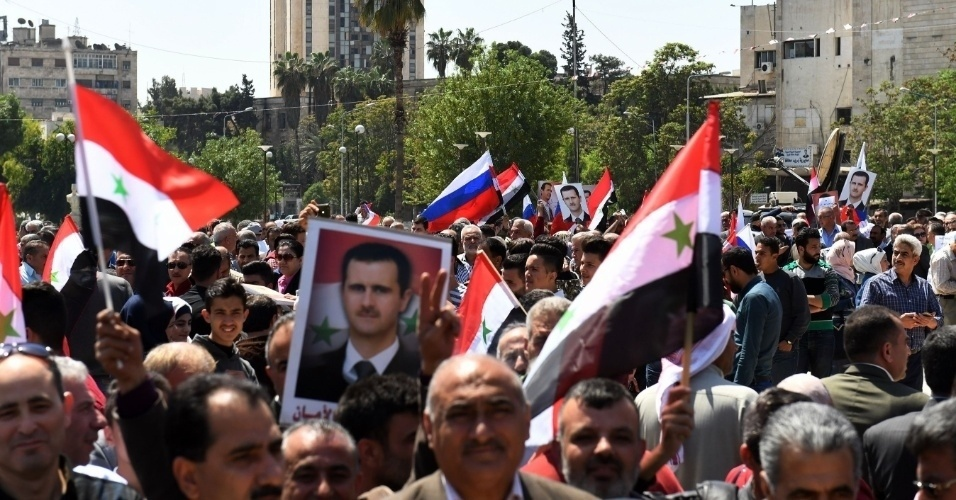 14.abr.2018 - Manifestantes carregam bandeiras e retratos do presidente Bashar al-Assad durante protesto contra o ataque de EUA, Reino Unido e França à Síria