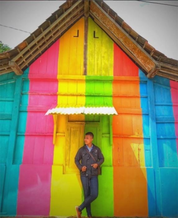 18.mai.2017 - Jovem posa em frente a uma das casas da favela Kampung Pelangi, que ganhou um colorido após uma ação do governo da Indonésia que pintou 232 casas da região