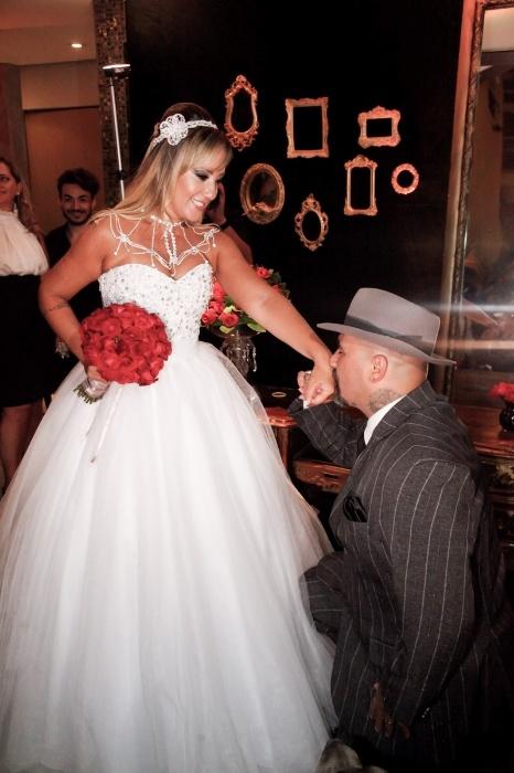 17.jan.2016 - De joelhos, o tatuador Fabiano dos Santos beija a mão da esposa, a ex-mallandrinha e apresentadora Vivi Fernandez