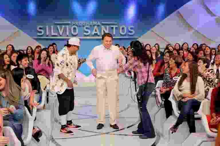"""9.set.2016 - Silvio Santos vai tirar a roupa no palco do seu programa, no SBT. O apresentador vai criticar o seu próprio look durante a atração. Que roupa feia. Escolhi muito mal. Porcaria de roupa. Olha aí, branco com creme. Não fica bem essa roupa, não pode mudar? Pode tirar?"""", questiona. Em seguida, Silvio começa a tirar o paletó, a gravata e o microfone. Veja mais a seguir - Reprodução/SBT"""