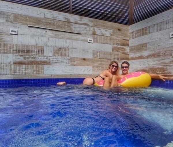17.out.2016 - Em outra foto, dessa vez ao lado do namorado Tony Villarejo, a modelo Bárbara Evans se debruça sobre uma boia na piscina, deixando novamente em destaque seu bumbum perfeito