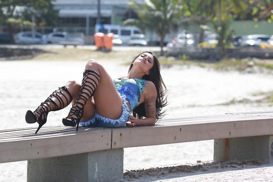 18.ago.2015 - De shortinho, sandálias pretas e body colorido, Aline Riscado posou em banco no meio da praia da Barra da Tijuca, no Rio de Janeiro, nesta terça-feira