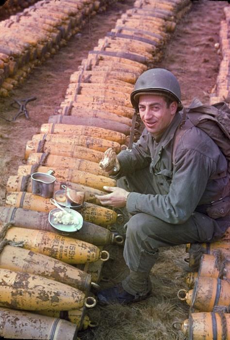 Mai.1944 - Soldado norte-americano faz uma refeição sobre estoque de munição na Inglaterra