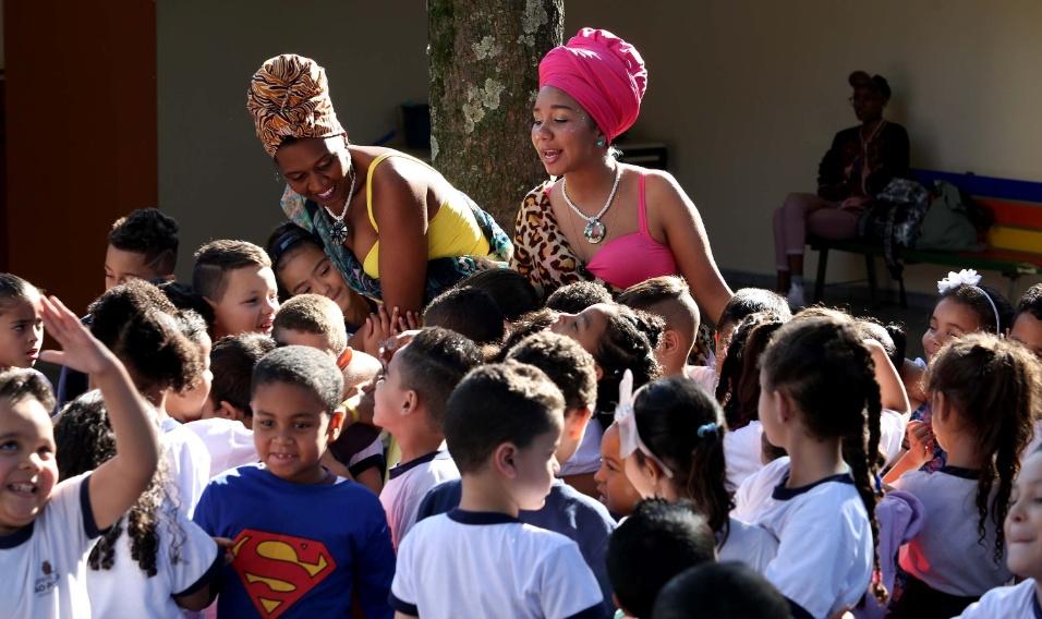 No final da ação, crianças se aproximam das princesas para vê-las de perto, abraçá-las e descobrir um pouco mais sobre o povo africano