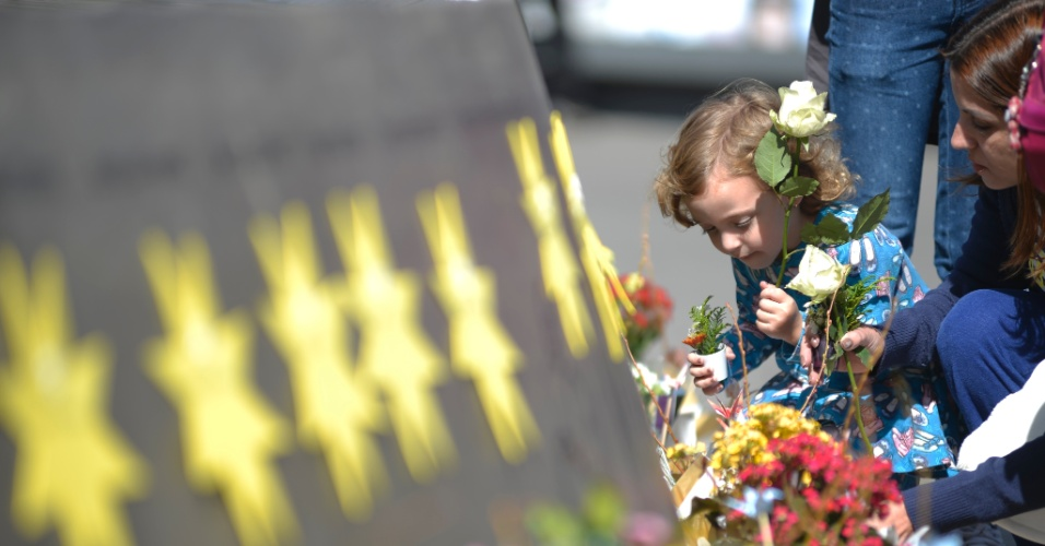 Criança oferece flores em homenagem a uma das vítimas do acidente da TAM em Congonhas