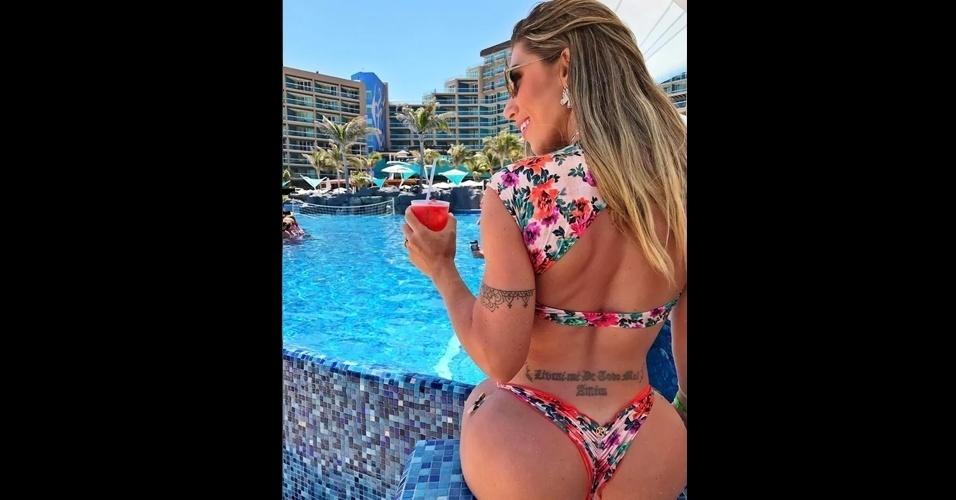 """25.mar.2017 - De férias em Cancún, Tati Minerato postou uma foto em que suas tatuagens ficaram em evidência. A beldade tem um desenho no braço e a frase """"Livrai-me do todo mal, amém"""" no cóccix"""