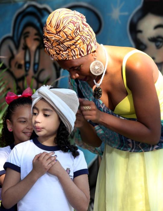 Princesa Funji coloca turbante em uma das estudantes da EMEI Batista Cepelos, em Heliópolis (SP)