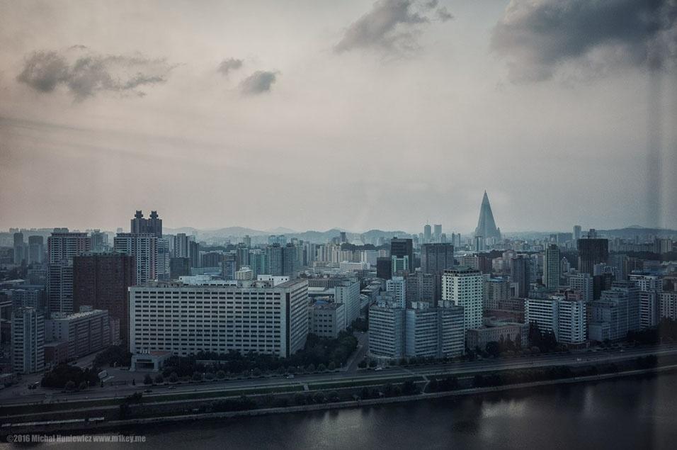 """40. """"Assim é Pyongyang vista do hotel Yanggakdo. À esquerda, o hotel Koryo, que teria se incendiado recentemente. Este é o lugar onde você vai ficar se você for chinês - os chineses têm mais liberdades do que ninguém. O hotel fica no centro da cidade, e os turistas que se hospedam ali pode andar em torno do bloco por conta própria, e fugir atravessando as ruas (embora oficialmente não seja permitido). À direita, o Ryugyong, também conhecido como o hotel da destruição. O prédio de 330 metros de altura está praticamente vazio, porque a Coreia do Norte não tem dinheiro para terminar a sua construção, iniciada em 1987"""""""