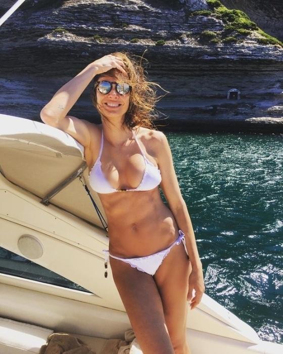 """24.ago.2016 - Luciana Gimenez postou uma foto em que aparece de biquíni branco em um cenário paradisíaco na Itália. A apresentadora, porém, usou o recurso do Photoshop para dar um truque e não mostrar um """"peitinho"""""""