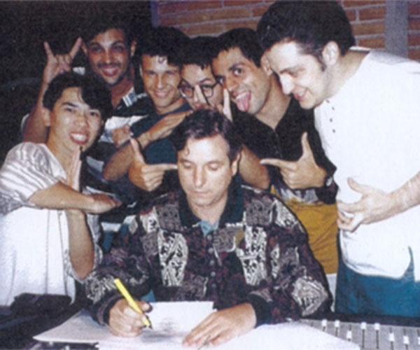 15.mai.1995 - Integrantes do grupo Mamonas Assassinas, ao lado do produtor, Rick Bonadio (à dir.), brincam durante assinatura do contrato do primeiro (e único) disco oficial da carreira da banda. João Augusto, da gravadora EMI, é quem assina o documento