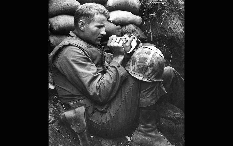Um soldado no campo de batalha alimenta um filhote de gato que perdeu a mãe durante a guerra