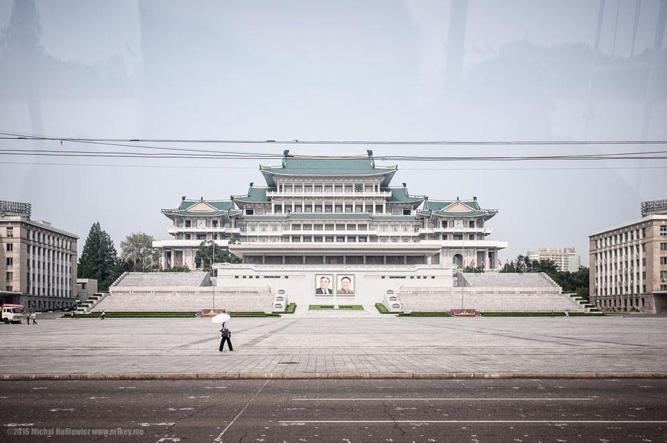 """51. """"No centro da capital - o Distrito Central - na Praça Kim Il-sung, a Grande Casa Popular de Estudos fica exatamente em frente à Torre Juche, do outro lado do rio Taedong. A biblioteca dentro daquele prédio tem alguns livros estrangeiros, mas é preciso uma permissão para levá-los, porque senão eles iriam contaminar as mentes norte-coreanas com ideias ocidentais. Aliás, eu já disse que o nome oficial da Coreia do Norte é República Popular Democrática da Coreia? No lugar em que Marx e Lênin já foram exibidos, agora estes dois - com o devido respeito - estão sempre sorrindo para nós com bondade"""""""