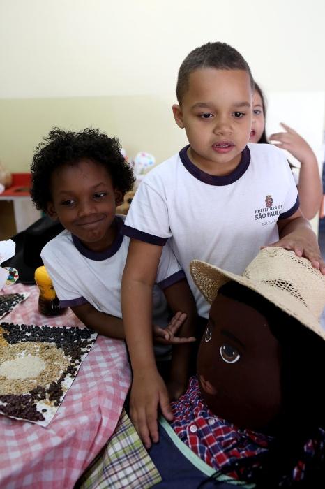 Professora Cibele. Dois alunos apresentam Azizi, o pai da família. Ele é sul-africano e, quando chegou ao Brasil, logo se apaixonou por Sofia