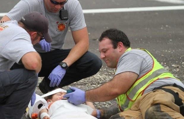 """7.set.2015 - O bombeiro Casey Lessard coloca em seu celular a animação infantil """"Happy Feet"""" para tentar acalmar criança após acidente"""