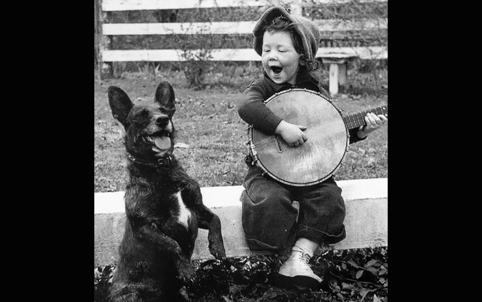 Garotinha toca banjo para o seu cachorro