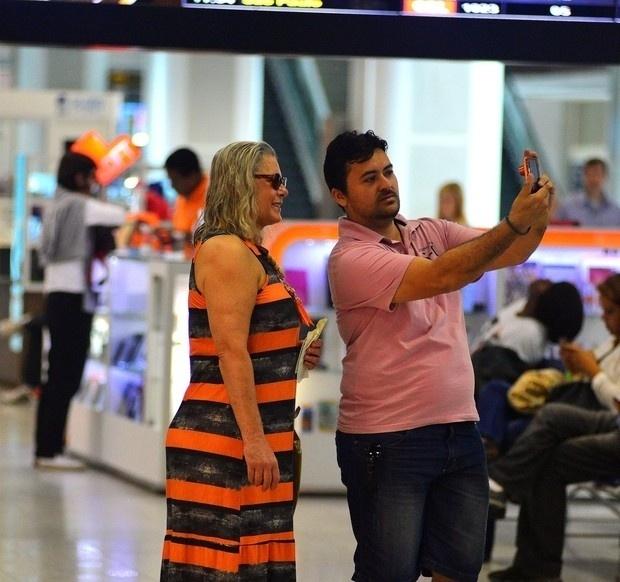 6.nov.2015 - De óculos escuros, Vera Fischer atende ao pedido de um fã para tirar foto no aeroporto Santos Dumont, no Rio de Janeiro