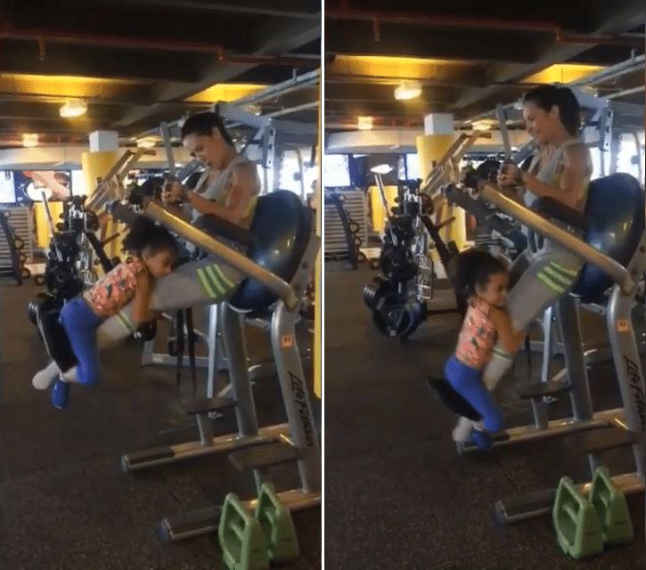 14.jan.2016 - Scheila Carvalho faz exercício para as pernas e glúteos e usa a filha como peso extra na academia