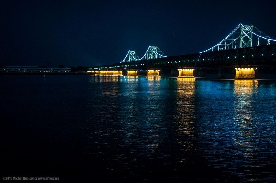 """5. """"A diferença entre Coreia do Norte e China se torna ainda mais evidente à noite, quando Dandong torna-se uma metrópole brilhante, enquanto a Coreia do Norte mergulha na escuridão. Na foto, a Ponte da Amizade Sino-coreana, que liga Dandong com a cidade de Sinuiju"""""""