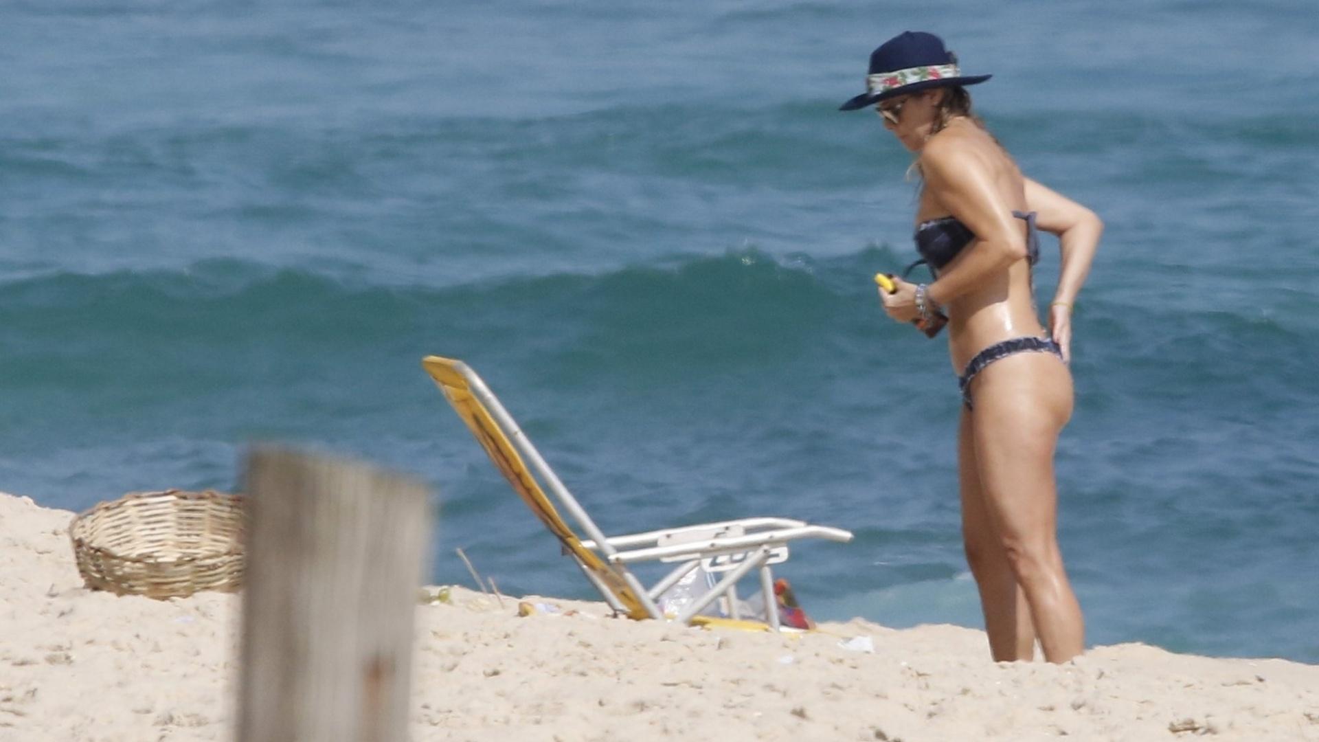8.dez.2016 - Christine Fernandes passa protetor solar em tarde de sol na praia da Macumba, no Rio de Janeiro