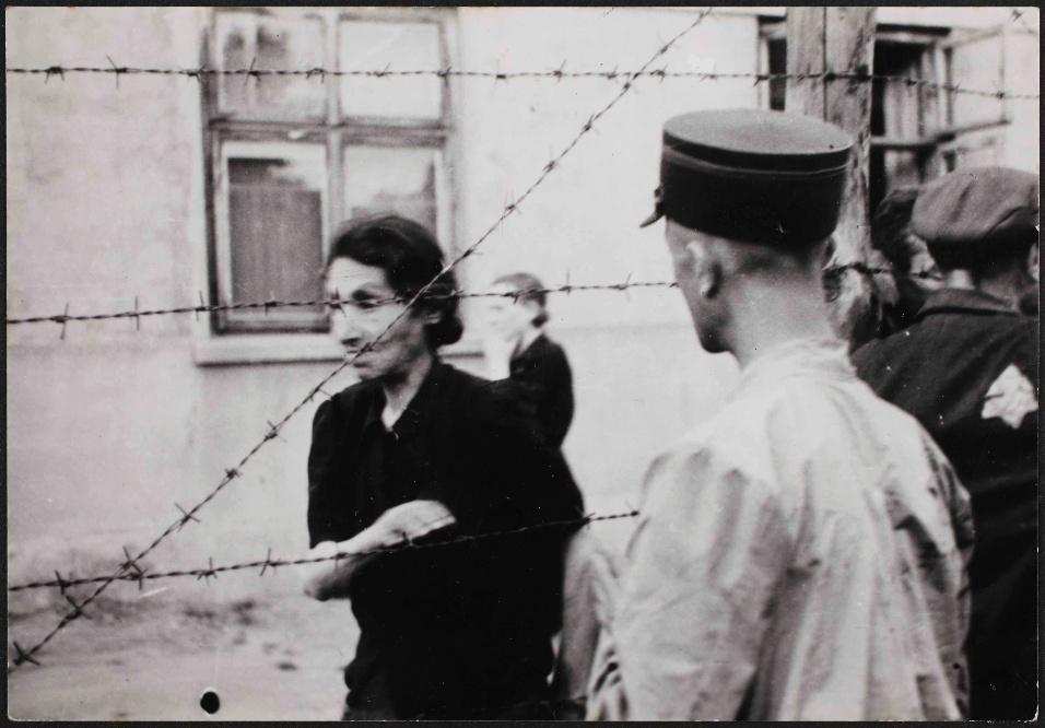 1942 - Guarda do gueto de Lodz, na Polônia, observa mulher do outro lado de barreira com arame farpado