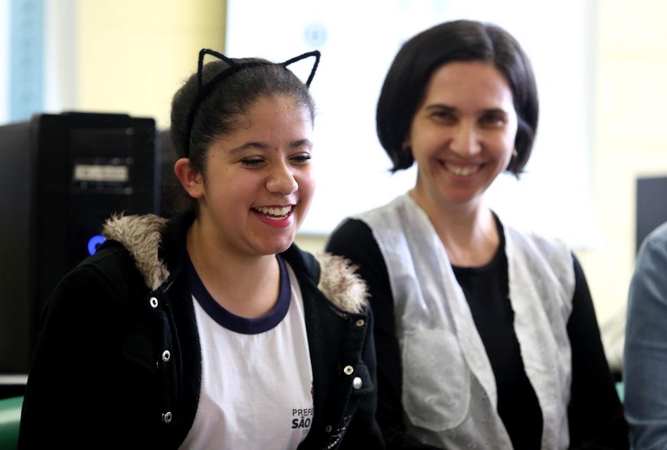 Professora Daniela Gissoni presta atenção em aluna ao falar sobre o aprendizado e a melhora que observou após sofrer bullying na escola