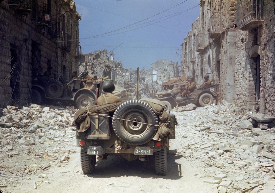Mai.1944 - Tropa dos Estados Unidos pilotam jipe sobre os destroços de uma cidade italiana não identificada