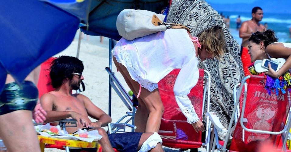 4.dez.2016 - Letícia Birkheuer recolhe o lixo antes de deixar a praia do Pepe, no Rio de Janeiro