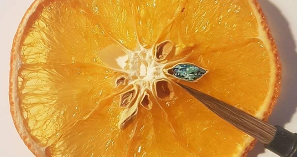 28. Em vez de chupar laranja, Hasan Kale prefere gastar seu tempo desenhando nas sementes da fruta