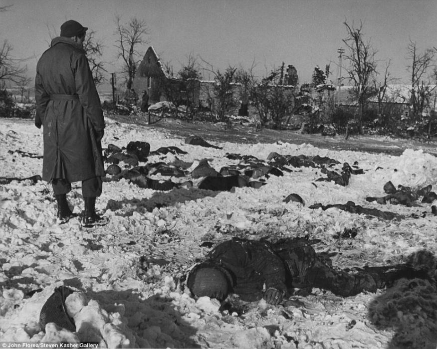 Soldado americano observa os corpos de colegas que foram fuzilados em janeiro de 1945
