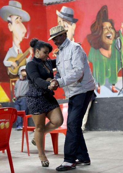 Luciana da Costa é uma das primeiras a arriscar passos de dança com um participante do samba durante a apresentação da roda Maria Cursi. No barracão, cada um dança como quiser: sozinho, colado ou apenas acompanhando a música na palma da mão