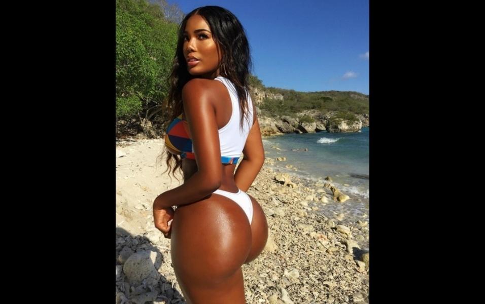 """8.ago.2017 - A modelo Monifa Jansen segue conquistando fãs na internet com fotos de seus ensaios de biquíni. Em uma praia de sua terra natal, em Curaçao, no Caribe, a modelo posou mostrando o bumbum e brincou: """"Como você gosta dos seus pãezinhos? Eu gosto dos meus tostados!"""". Milhares de fãs responderam dizendo que Monifa é """"perfeita"""", """"espetacular"""" e até mesmo """"um sonho virando realidade"""""""
