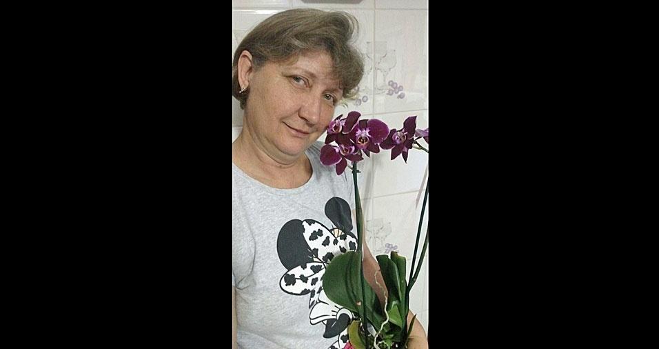 """Lucimara Polidoro, de Curitiba (PR), declara seu """"amor pelas flores"""" posando para a foto ao lado da linda orquídea Phalaenopsis"""