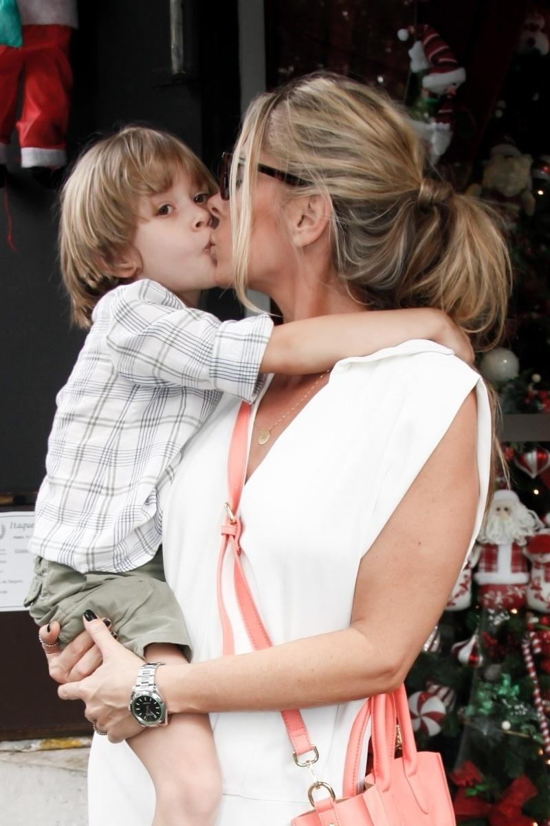 18.dez.2015 - A apresentadora Adriane Galisteu deu um selinho no filho Vittorio durante evento beneficente em São Paulo