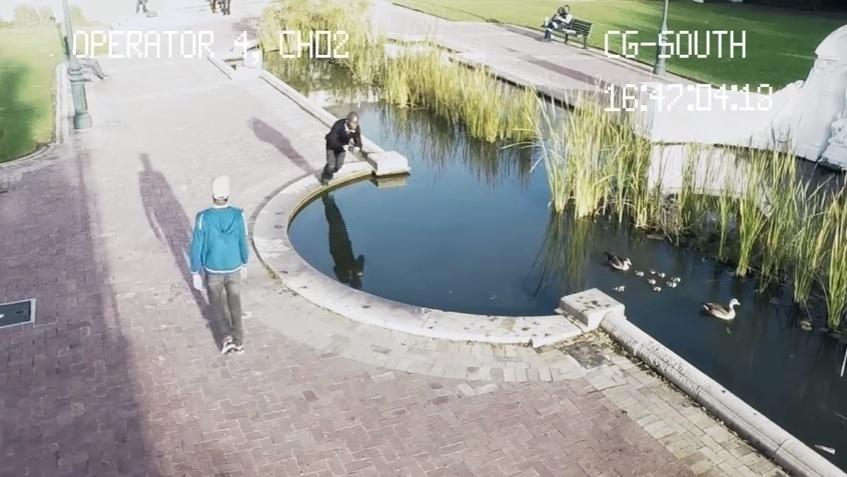 Na imagem, um homem mexendo em seu celular não percebe um lago a sua frente e acaba caindo.
