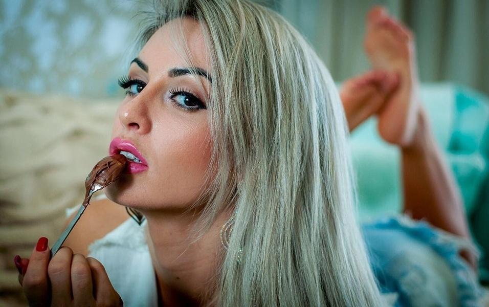 """13.abr.2017 - Perto do domingo de Pácoa, a campeã do concurso Musa do Brasil 2016, a loirinha Iara Ferreira, fez um ensaio sensual em seu apartamento e revelou um vício seu: o chocolate. A gata, que é adepta de uma rotina fitness, diz que essa é a única """"besteirinha"""" que ela ela se permite comer quase que diariamente. """"Eu treino seis vezes por semana, e são exercícios bem intensos que vão desde o aeróbico à musculação"""", contou a gata"""